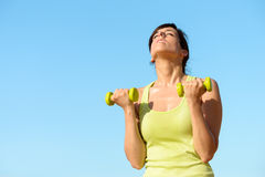 Fitness woman training biceps on summer Stock Photography