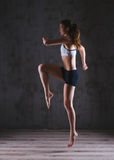 Fitness woman training in dark studio. Young girl posing on black background Royalty Free Stock Photos