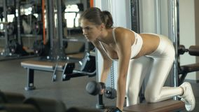 Fitness woman training with heavy dumbbells for training muscle back in gym club. Woman bodybuilder lifting weights dumbbells on modern fitness club stock footage