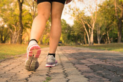Fitness woman training and jogging in summer park, close up on running shoes. Healthy lifestyle and sport. Royalty Free Stock Photos