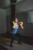 Fitness woman training by kettlebell. Fit young lady doing crossfit exercise. Royalty Free Stock Images
