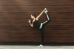 Woman training yoga in std bow pose outdoors. Fitness, woman training yoga in std bow pose at wooden wall background, copy space. Young slim girl makes aerobics royalty free stock photography