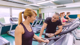 Fitness woman in treadmill talking with hadsome Stock Photography