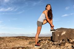 Fitness woman tying running shoes laces for race. Fitness woman tying running shoes laces getting ready for race marathon in desert summer landscape. Asian trail royalty free stock photography