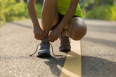 Fitness woman tying shoelace on morning tropical forest trail Royalty Free Stock Photo