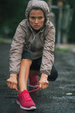 Fitness woman tying shoelaces outdoors Stock Photos