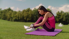 Fitness woman tying shoelaces on yoga mat in summer park. Fitness woman preparing for fitness training. Asian girl tying laces on her running shoes. Sporty stock footage