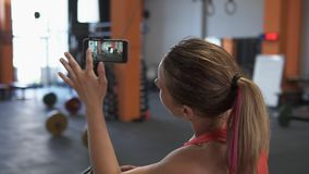 Fitness woman uses smartphone to shoot video workout in gym stock footage