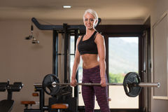 Fitness Woman Using Barbell Exercising Back Inside Gym Royalty Free Stock Images