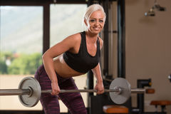 Fitness Woman Using Barbell Exercising Back Inside Gym Stock Photo