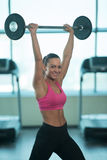 Fitness Woman Using Barbell Exercising Shoulders Inside Gym Royalty Free Stock Images