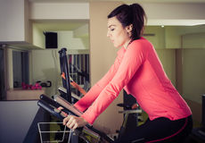 Fitness woman using cycling exercise bike at gym Stock Image