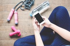 Fitness woman using mobile device, Sport equipment, Bottle water on wood. Floor Stock Image
