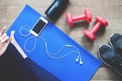 Fitness woman using mobile device, Sport equipment, Bottle water on wood. Floor Stock Photography