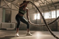 Athlete working out with battle ropes at cross gym. Fitness woman using training ropes for exercise at gym. Athlete working out with battle ropes at cross gym stock photography