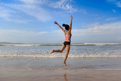Fitness woman wear swimsuit jumping on beach. Young fitness woman wear swimsuit jumping on beach Royalty Free Stock Images