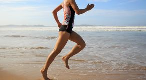 Fitness woman wear swimsuit running on beach. Young fitness woman wear swimsuit running on beach Royalty Free Stock Photography