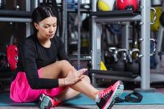 Fitness woman woman doing leg self massage at gym. Stock Image