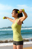 Fitness woman work out on beach. Woman training shoulders with dumbbells on beach. Summer work out, fitness and exercising with weights outdoor. Caucasian sport Royalty Free Stock Photography