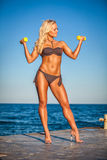 Fitness woman working out on beach in summer Royalty Free Stock Image