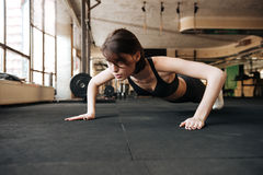 Fitness woman working out and doing pushups in gym Stock Photos