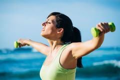 Fitness woman working out with dumbbells outdoor Stock Photo