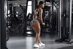 Fitness woman working out in gym. Active girl exercising. buttocks in thong stock image