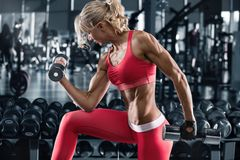 Fitness woman working out in gym, doing exercise for biceps. Muscular athletic girl.  royalty free stock photos