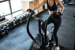 Fitness woman working out on spinning bicycle in gym royalty free stock photos