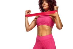 Muscular young fit sports woman athlete in pink sportswear with bands or expander in gym. Copy space for fitness stock photos