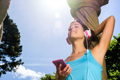 Fitness woman workout rest and relax. Relaxed fitness woman taking a rest and listening music with smartphone and headphones after workout. Sporty happy girl Royalty Free Stock Images