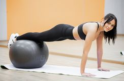 Fitness woman. Young attractive woman doing push ups using ball.  stock photography