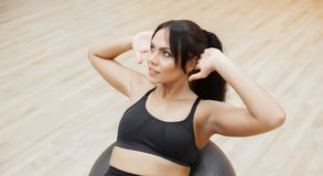 Fitness woman. Young attractive woman doing push ups using ball.  stock photo