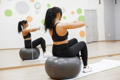 Fitness woman. Young attractive woman doing push ups using ball.  royalty free stock photo