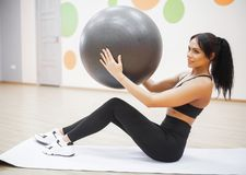 Fitness woman. Young attractive woman doing push ups using ball.  royalty free stock images