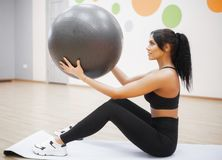 Fitness woman. Young attractive woman doing push ups using ball.  royalty free stock photos