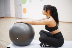 Fitness woman. Young attractive woman doing push ups using ball.  royalty free stock photography