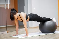 Fitness woman. Young attractive woman doing push ups using ball.  royalty free stock image