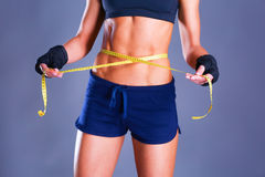 Fitness womans beautiful body with measure tape Stock Photography