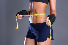 Fitness womans beautiful body with measure tape Royalty Free Stock Photography