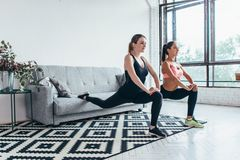 Fitness women doing front forward one leg step lunge exercises workout.  royalty free stock photo