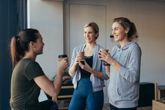 Fitness women drinking coffee after workout in a gym Royalty Free Stock Photography