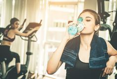 Fitness woman drinking fresh water on working out break Stock Photos