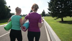 Fitness women with excercise mats going training stock footage