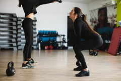 Fitness women kettlebell workout. In gym. Two women cross fitness workout Royalty Free Stock Photo