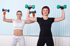Fitness women lifting dumbbells Stock Images