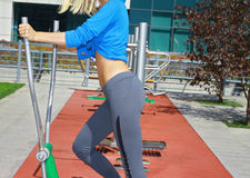 Fitness women in outdoor gym,  flat belly, stomach ,trained buttocks, perfect body, street workout. Sport, fitness, active lifesty Royalty Free Stock Photos