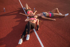 Fitness women resting on floor. Tired athletes lying after a gym workout together in circle in stadium. Stock Photo