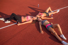 Fitness women resting on floor. Tired athletes lying after a gym workout together in circle in stadium Royalty Free Stock Photo