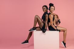 Fitness women resting after workout. Two fit women sitting on a box smiling and looking at camera with copy space Royalty Free Stock Images